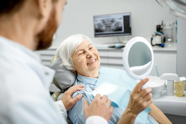 Woman smiling in mirror after receiving dental implant secured dentures from Dr. Turella