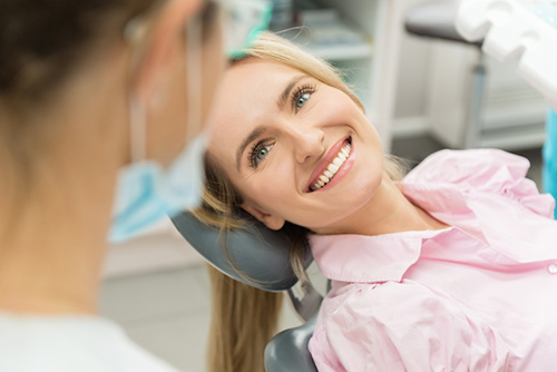 A woman smiling in her dental chair at Turella Oral Surgery in Port Angeles, WA.